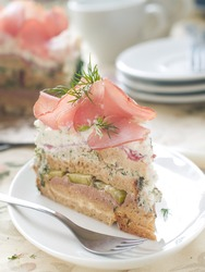 Slice of sandwich cake with prosciutto and dill for appetizer, selective focus