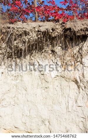 Slice of soil, rock layers, agroindustrial background, sectional history of the earth