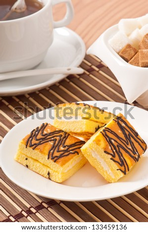 Slice of sponge cake with tea and sugar