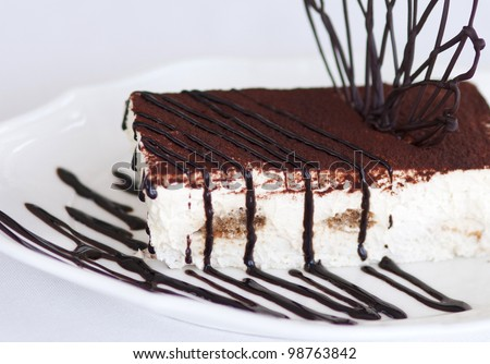 Slice of tasty chocolate tiramisu cake traditional Italian biscuit dessert on white plate on table in restaurant. Piece of unhealthy calories fat food .