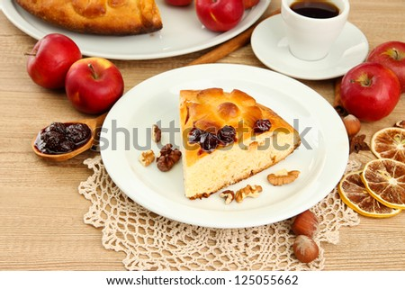 slice of tasty homemade pie with jam and apples and cup of coffee, on wooden table