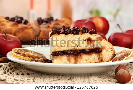 slice of tasty homemade pie with jam and apples, on wooden table