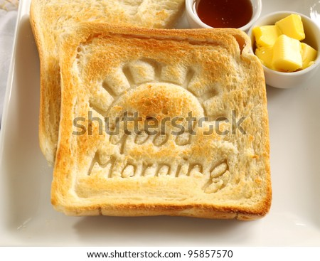 Slice of toast with Good Morning carved into it with butter and honey.