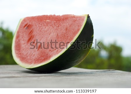 slice of watermelon on wooden table, mediterranean garden background