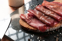 Slice of wholemeal bread with bresaola (dried beef) on a black granite cutting board. Bresaola is a famous Italian salami with reduced fat content