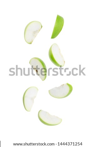 Slice ripe green apple falling isolated on white background with clipping path.