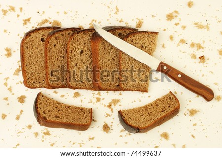 Sliced and crumbled rye bread with kitchen knife on the white table with crumbles