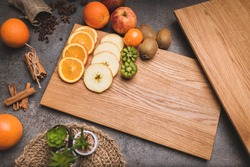 Sliced and fresh fruit lying on an oak chopping board. Moody dark photo from above. Extras arranged on the sides. Healthy food. Place for inscriptions. Copy space.