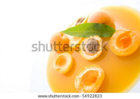 Sliced and whole apricots on plate representing soup concept.