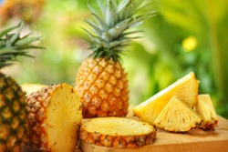 Sliced and whole of Pineapple(Ananas comosus) on wooden table with blurred   garden background.Sweet,sour and juicy taste.Have a lot of fiber,vitamins C and minerals.Food,Fruits or healthcare concept.