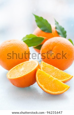 Sliced and whole orange with green leaves