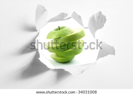sliced apple fruit behind a hole in blank paper