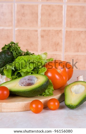 Sliced avocado and fresh vegetables on a wooden board  on a kitchen table