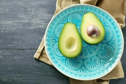 Sliced avocado on plate, on wooden background