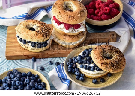 sliced bagels with cream cheese and fresh wole blueberries and red raspberries Zdjęcia stock ©