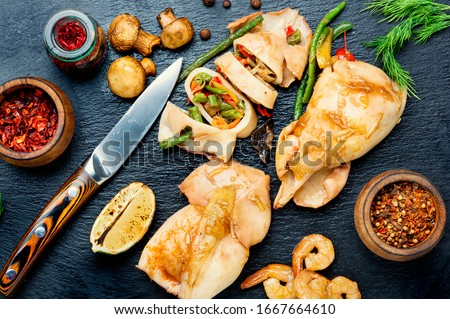 Sliced baked squid with vegetables on a slate board.Squid stuffed with mushrooms.Bbq calamary Сток-фото ©