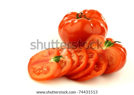 sliced beef tomato and a whole one on a white background