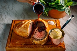 Sliced Beef Wellington with the pouring sauce and the mash potatoes