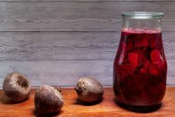 Sliced beetroot in glass jar. Preparing fermented beetroot liquid and picked slices.