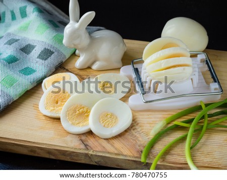 sliced boiled eggs with egg-cutter and white ceramic rabbit on green bunch onion and towel on cutting board black backgground. prepearing eggs for salad
