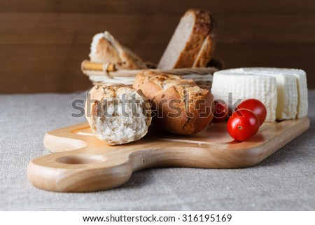 Sliced bread on wood, homemade cheese and tomatoes #316195169