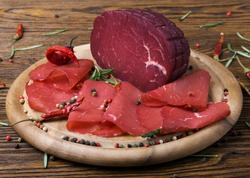 Sliced bresaola with a sprig of rosemary and red pepper on a wooden board