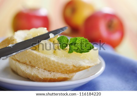 Sliced bun with apple jam and knife on plate. Small shallow dof.