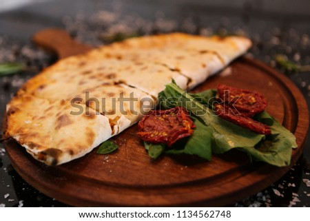 Sliced calzone pizza on a rustic wooden serving tray, selective focus