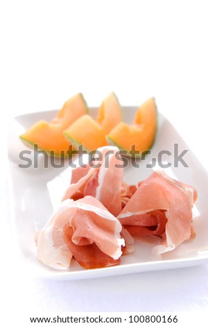 Sliced cantaloupe with piles of prosciutto, a type of Italian cured ham