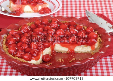 Sliced cherry cheesecake in a baking dish with piece in background