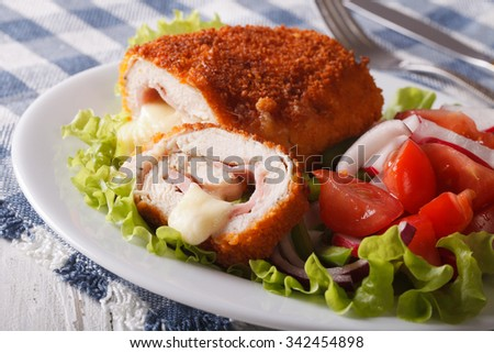 Sliced Chicken cordon bleu and a salad on a plate close-up. horizontal