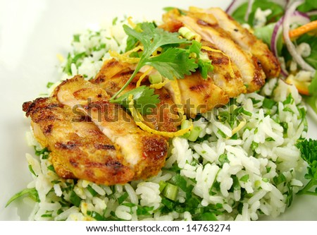 Sliced chicken tikka on a bed of lemon coriander rice with salad.
