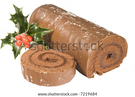 Sliced Christmas yule log with holly and berries on white background