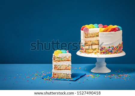 Sliced confetti Birthday cake  with rainbow colored icing and Sprinkles over a blue background. Foto stock ©