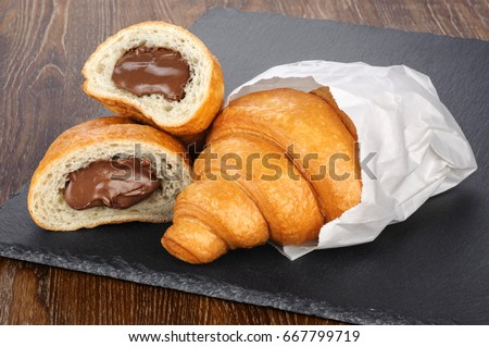 Sliced croissant with chocolate on the background of a slate board.