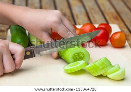 sliced cucumber. Child  cut cucumber  knife