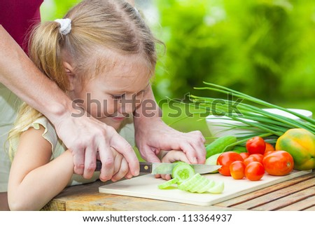 sliced cucumber. Mother teaches daughter  knife cut cucumber