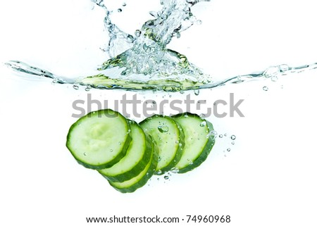 sliced cucumber splashing water isolated on white background - stock photo
