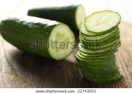 sliced cucumber stack on wooden plate.