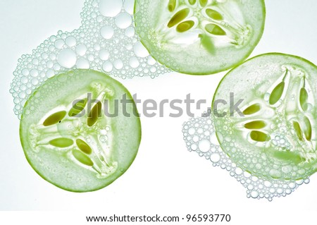 Sliced cucumbers in water isolated on a white background.