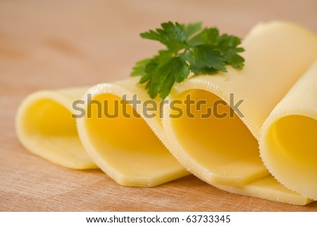 Sliced delicious edam cheese on wooden board with selective depth of field