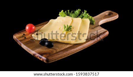 Sliced Edam cheese on cutting board isolated with clipping path