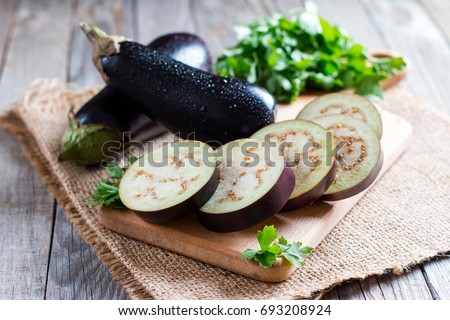 Sliced eggplant on wooden cutting board #693208924