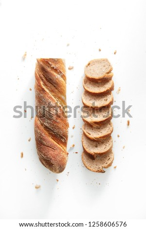 Sliced french bread isolated on a white background. Baguette slices and crumbs viewed from above. Top view