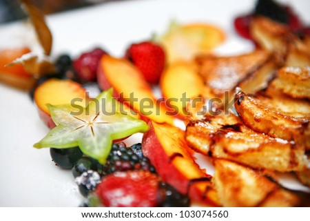 Sliced French Toast bread with powdered sugar and mixed fruit on white plate - stock photo