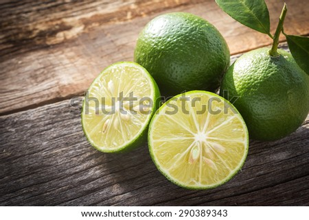 Sliced fresh limes on old wooden background. With dark vignette.