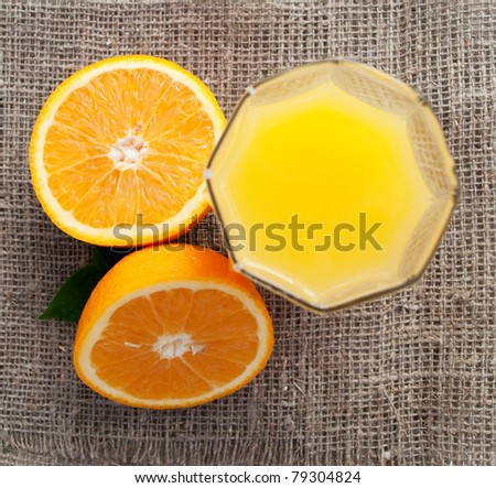 sliced fresh orange and glass of juice on stylish cloth