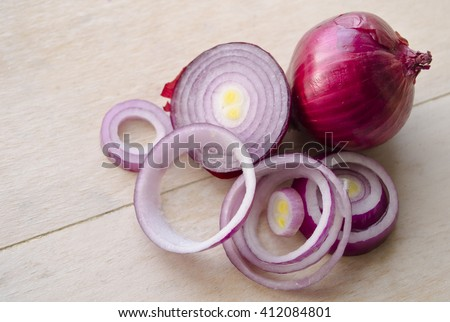 Sliced fresh purple onion isolated on wooden background. Full and chopped onion. Closeup. Yalta onion, cut onion, sliced onion, carved onion, dissected onion, onion peel, onion skins, crimean onion.