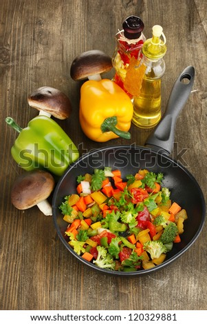 Sliced fresh vegetables in pan with spices and ingredients on wooden table