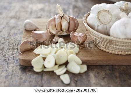 sliced garlic, garlic clove, garlic  bulb in wicker basket place on chopping block on vintage wooden background
